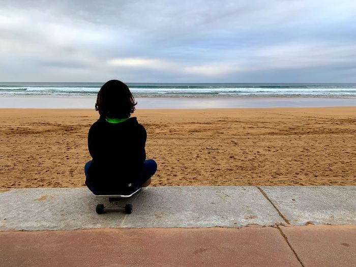 Rear view of girl sitting on skateboard at beach