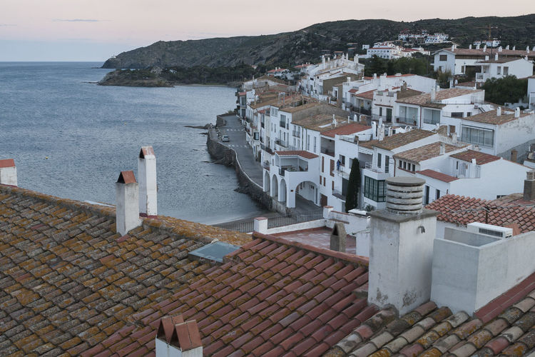 High angle view of townscape by sea against sky riva pitxot cadaquès alt empordà. girona. spain.
