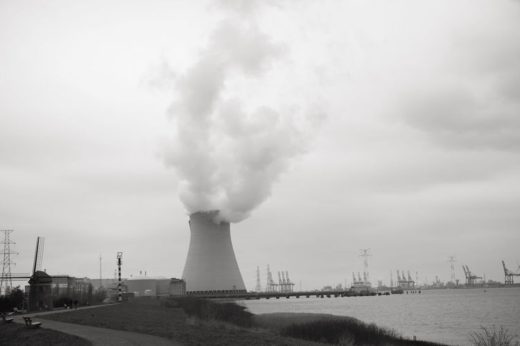 May 2016, Doel, Antwerp, Belgium, Cooling towers of the nucleair power plant in Doel next to the river Scheldt Smoke - Physical Structure Environment Pollution Environmental Issues Sky Factory Industry Smoke Stack Emitting Building Exterior Architecture Built Structure Nature Air Pollution Day Science Fuel And Power Generation Outdoors No People Cloud - Sky Fumes Cooling Tower Ecosystem  Atmospheric