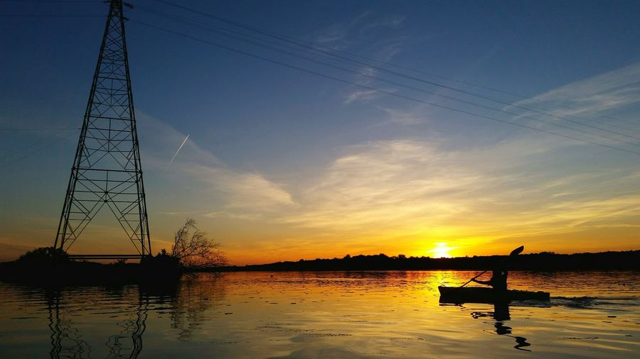 Silhouette person kayaking in river by electricity pylon against sky during sunset