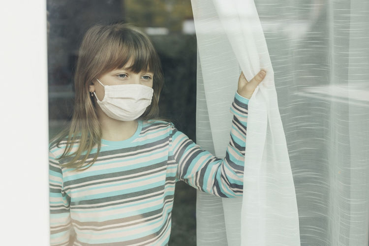 A school-age girl in a protective medical mask looks out the window.