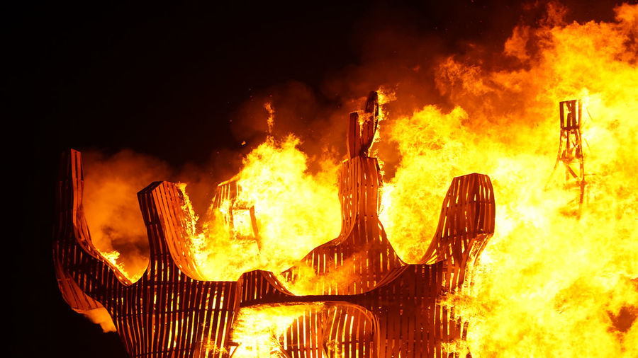 Panoramic view of fire burning at night
