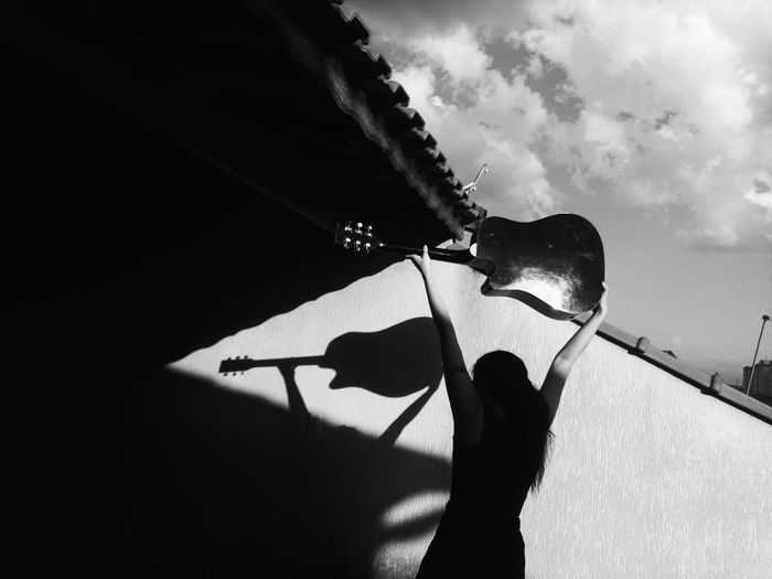 Low angle view of silhouette man holding umbrella against sky