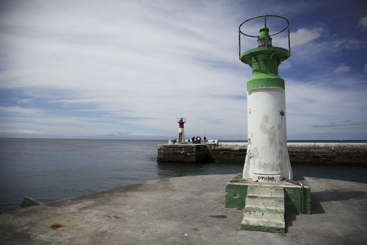 Lighthouse on shore against calm sea