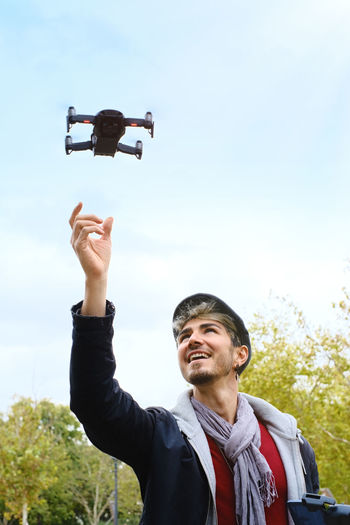 Smiling man looking at quadcopter
