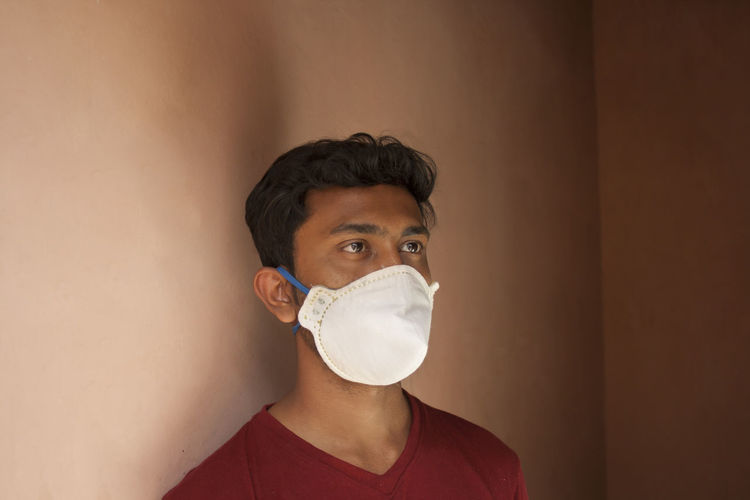 Young man with mask against wall