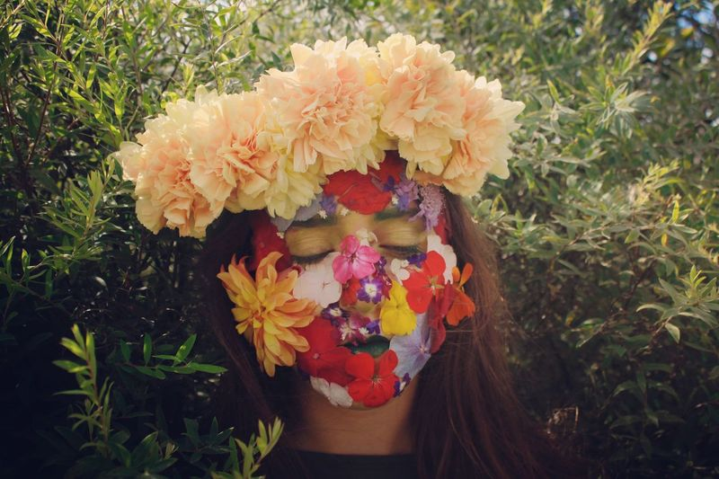 Close-Up Of Teenager Wearing Flowers Against Plants