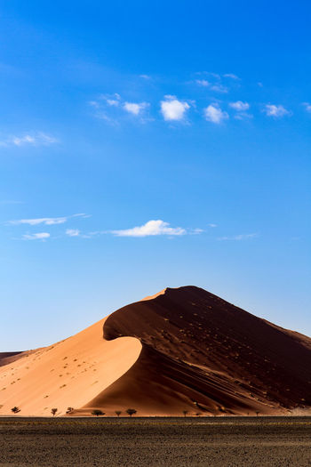 Landscape and sand dune against blue sky