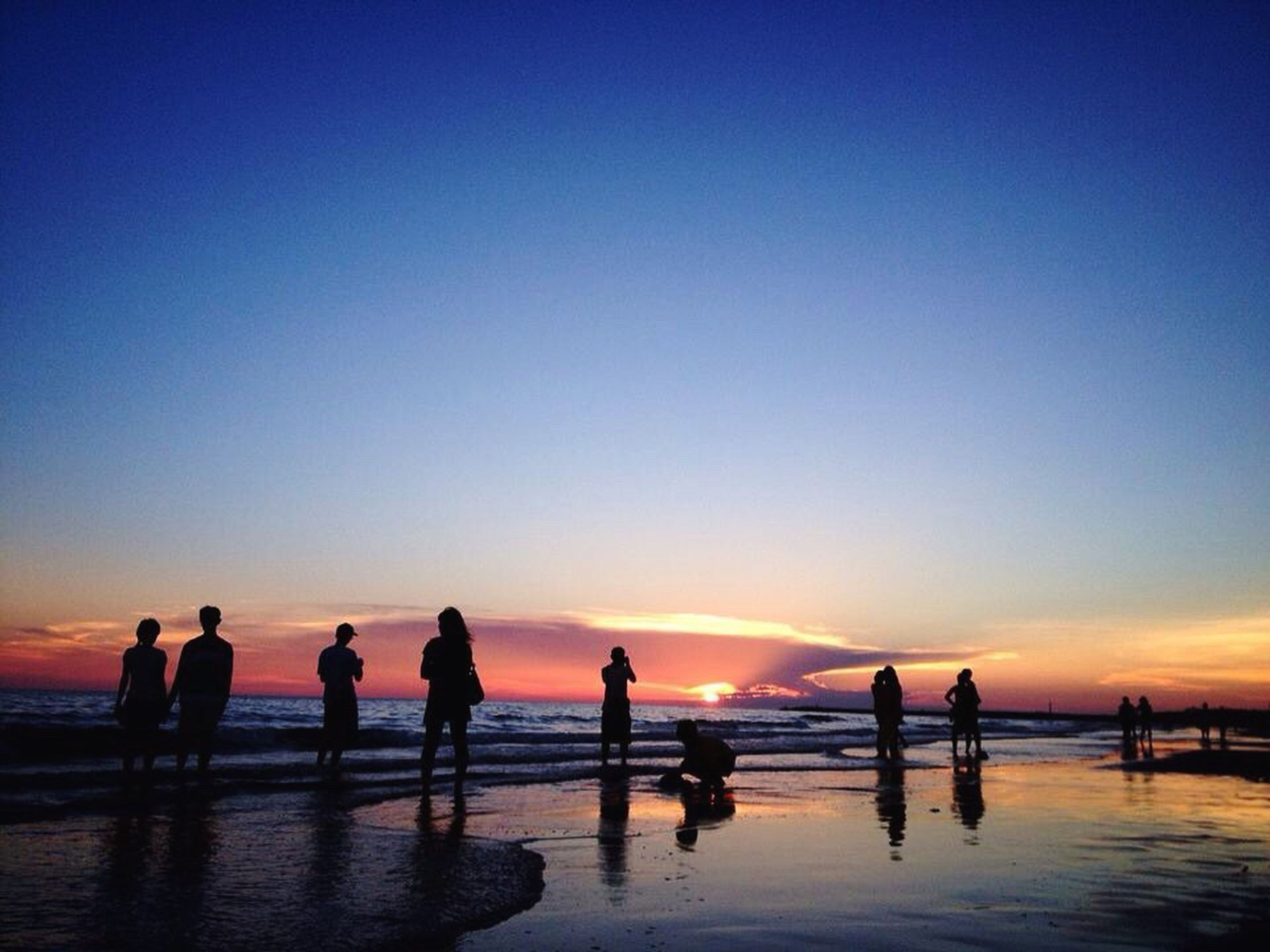 sea, sunset, water, silhouette, horizon over water, beach, copy space, orange color, scenics, tranquility, tranquil scene, beauty in nature, clear sky, men, vacations, leisure activity, sky, waterfront, reflection