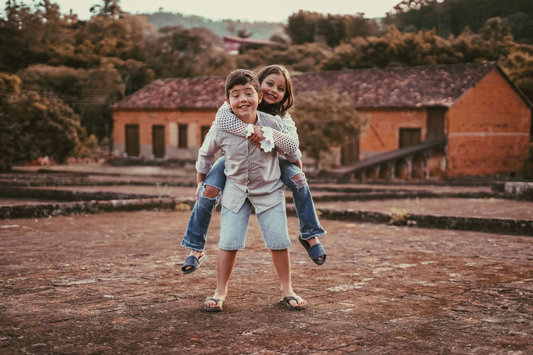 Portrait of brother with sister piggyback while standing outdoors