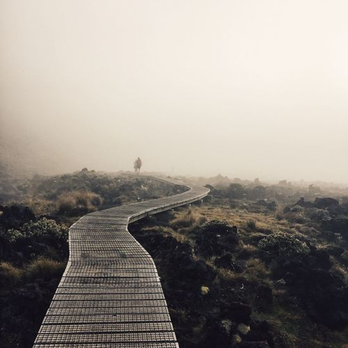 Boardwalk on field against sky during foggy weather