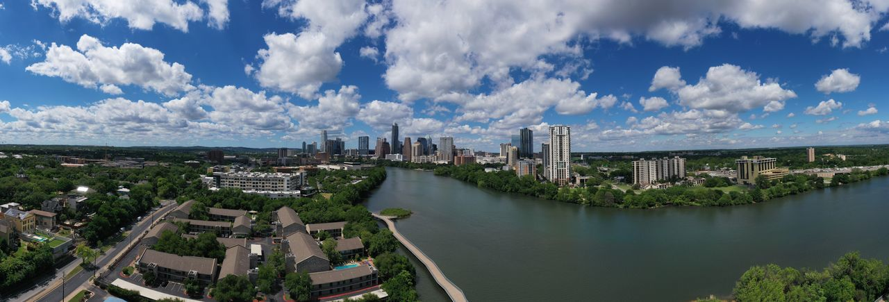 Panoramic view of buildings against cloudy sky