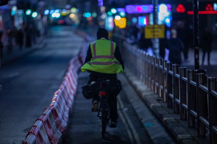 Rear view of man riding bicycle on street at night