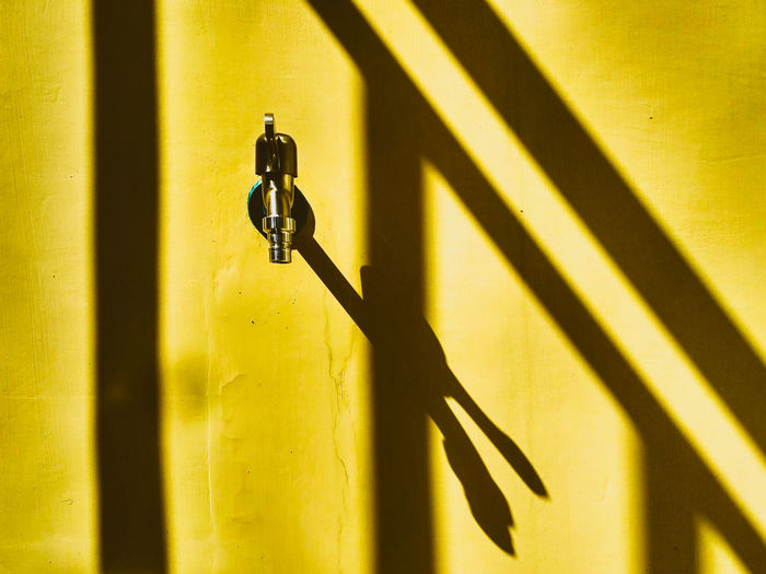 Close-up of metal faucet on yellow wall during sunny day