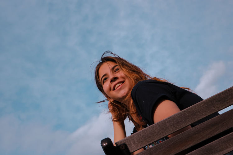 Low angle portrait of young woman against sky