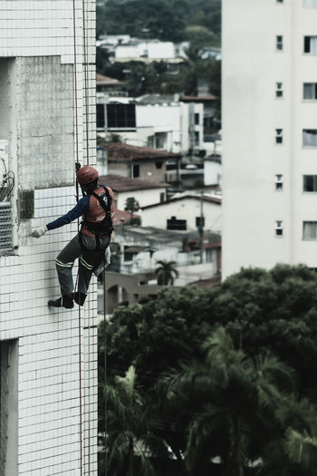 Low angle view of worker against buildings in city