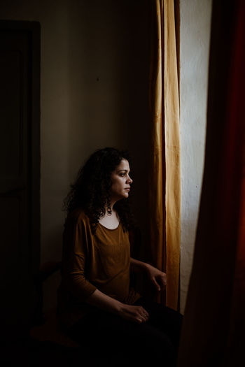 Thoughtful woman looking through window while standing in dark at home