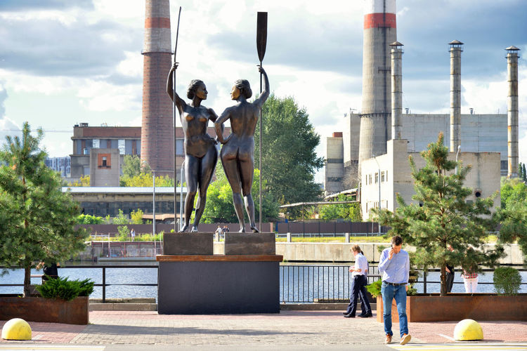 Women With Paddle, Man With Phone Street People City Moscow Travel Statue Day Outdoors Sculpture Chimney Europe Russia Eastern Europe Moscow, Russia A New Perspective On Life RU643_MOSCOW_AK RU643_RUSSIA_AK Streetwise Photography