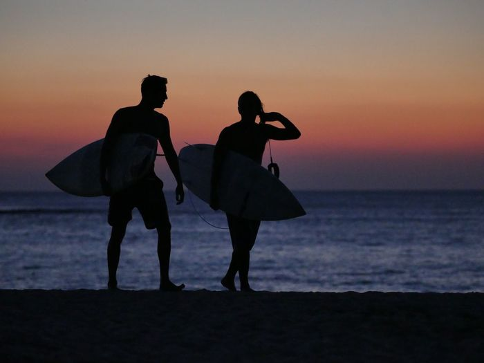 Silhouette friends with surfboards walking at beach against orange sky