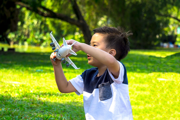 A boy playing with airplane dreams of pilot aviator traveling in nature park background Boys Child Childhood Day Grass Growth Holding Nature One Boy Only One Person Outdoors Park - Man Made Space People Real People Technology Tree Weapon
