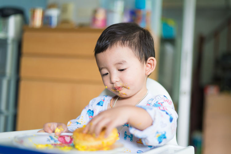 Innocent boy having food while sitting on high chair at home