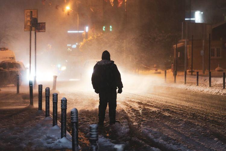 Rear view of man walking on street during winter at night