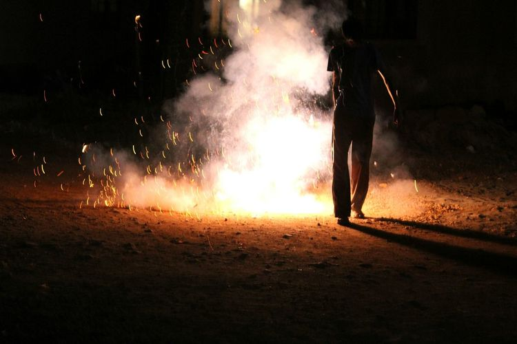 Rear View Of Man Burning Crackers On Field At Night