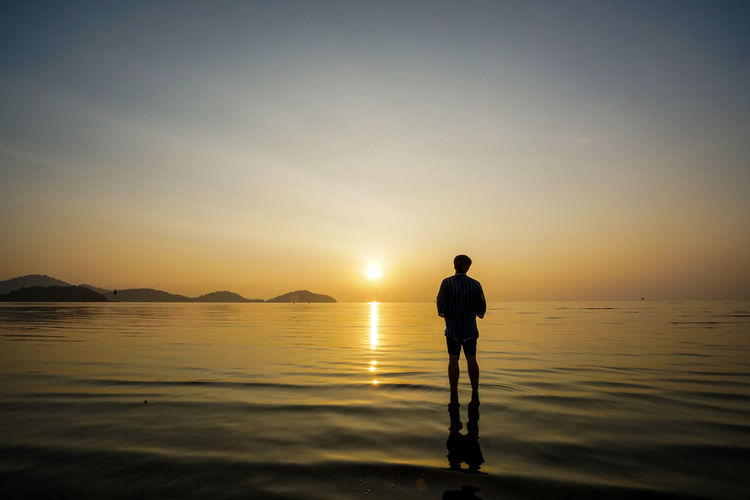 Water Sky Sunset One Person Standing Sea Beauty In Nature Scenics - Nature Silhouette Real People Leisure Activity Tranquility Tranquil Scene Rear View Reflection Beach Nature Lifestyles Men Sun Horizon Over Water Contemplation Looking At View