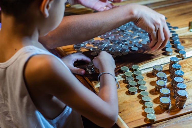 Many coins on a wooden table. Adult Board Game Casual Clothing Chess Game High Angle View Holding Human Hand Indoors  Leisure Activity Leisure Games Lifestyles One Person Playing Real People Relaxation Table Women Wood - Material