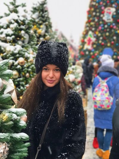 Portrait Of Young Woman Standing Amidst Christmas Trees During Winter