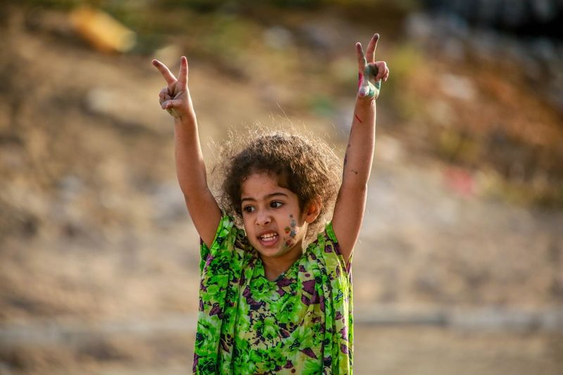 Girl showing peace signs while standing outdoors