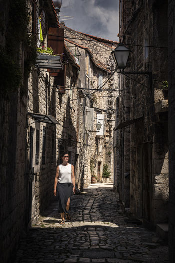 Woman standing on street amidst buildings