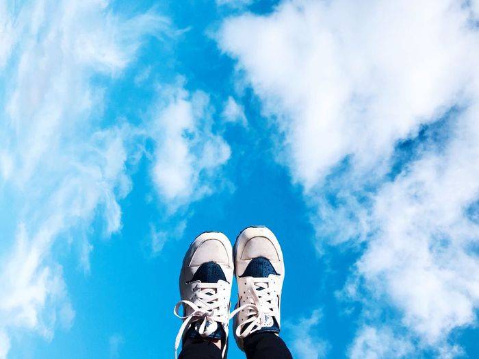 Low section of man wearing shoes against blue sky