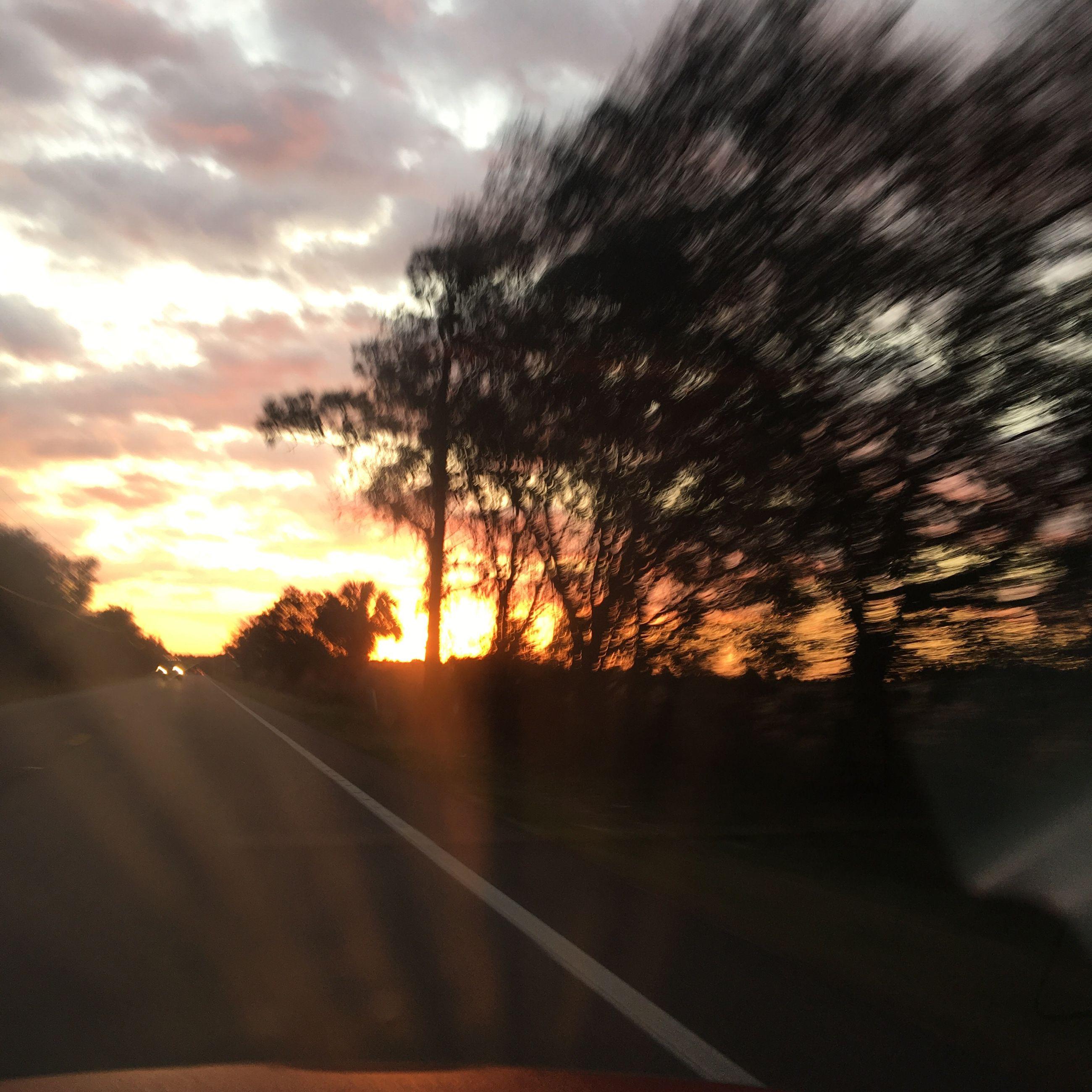sunset, transportation, road, sky, tree, car, sun, silhouette, the way forward, orange color, cloud - sky, sunlight, land vehicle, street, road marking, mode of transport, sunbeam, cloud, nature, diminishing perspective