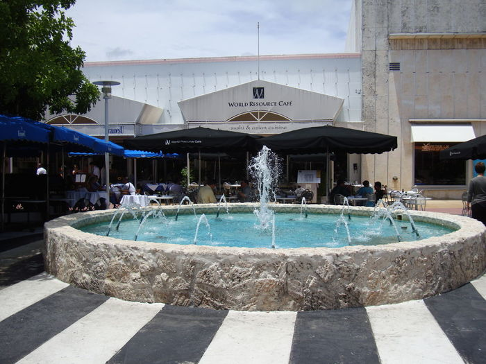 Fountain in swimming pool against buildings in city