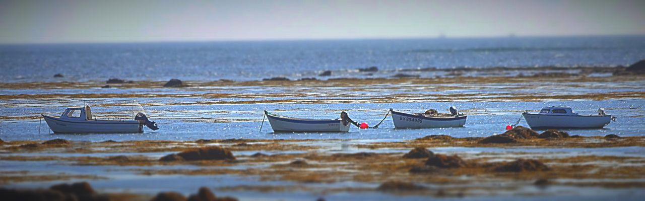 Panoramic Shot Of Boats Moored At Beach Against Sky