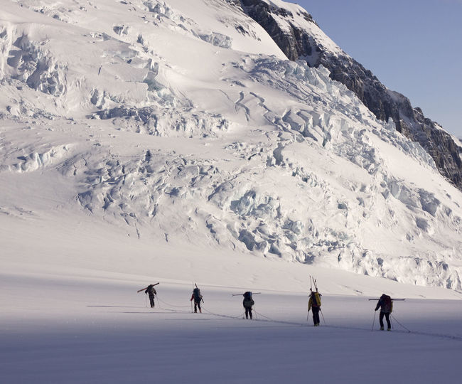 People hiking on snowcapped mountain