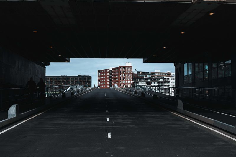 Empty road amidst buildings in city