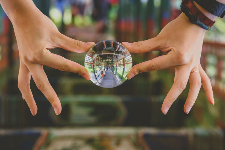 Close-up of hands holding crystal ball with reflection