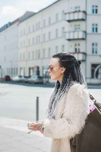 Profile of a fashion forward young woman walking on a street Braids Cool Fashion Hair Hairstyles Modern Profile Stylish Walking Around Artificial Beautiful Woman City Coat Fashionista Fur Hair Hairstyle House Long Hair Outdoors Street Streetphotography Walking Warm Clothing Young Adult