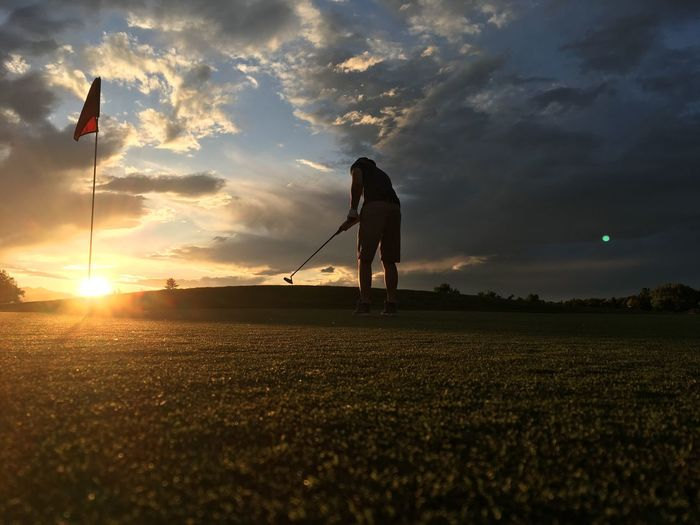 Man playing on golf course against sky during sunset
