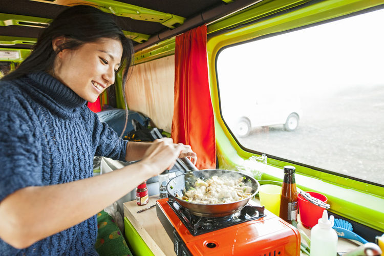 Midsection of woman preparing food in car