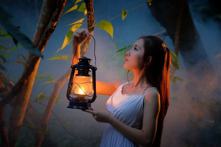 Close-Up Of Young Woman With Illuminated Lantern Standing By Tree