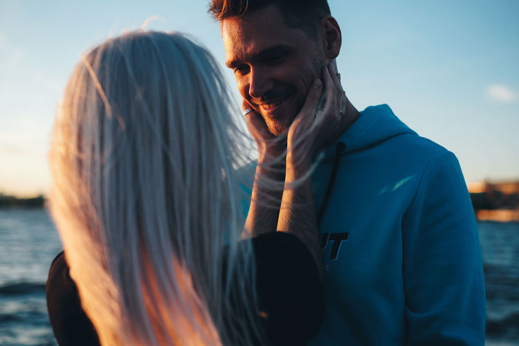 Couple in love on the pier, sunset time, water background Real People Lifestyles Beard Young Men One Person Men Water Leisure Activity Young Adult Sky Adult Casual Clothing Facial Hair Nature Portrait Waist Up Males  Focus On Foreground Outdoors Contemplation