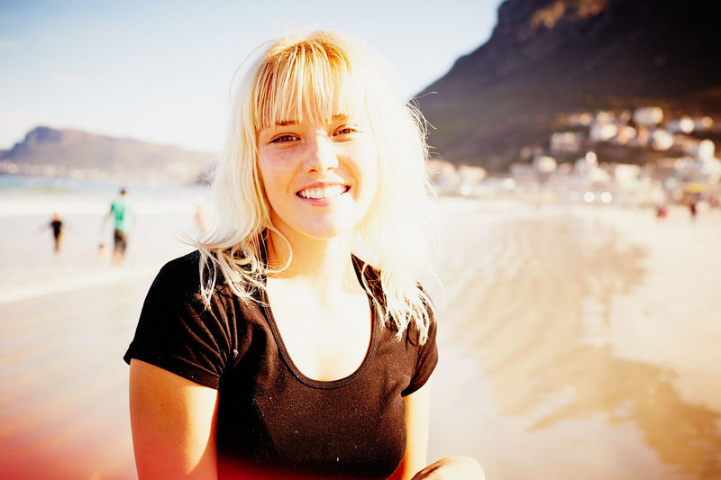 Beach Beautiful Woman Beauty In Nature Blond Hair Close-up Day Focus On Foreground Front View Happiness Incidental People Leisure Activity Lifestyles Looking At Camera Nature One Person Outdoors Portrait Real People Sea Smiling Standing Vacations Water Young Adult Young Women