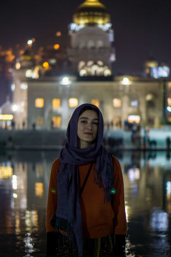 Portrait of young woman standing against illuminated building at night