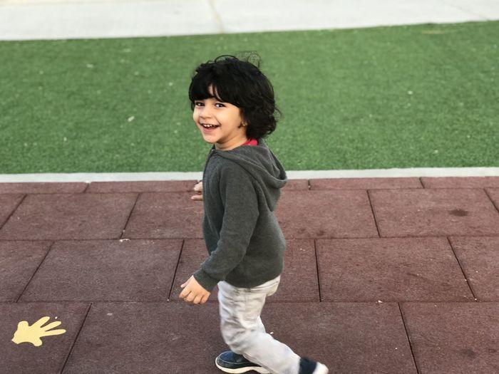 Portrait of cheerful boy walking on footpath