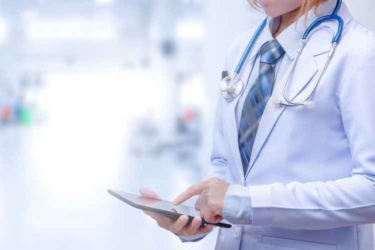 Adult Clothing Communication Digital Tablet Doctor  Focus On Foreground Healthcare And Medicine Healthcare Worker Holding Hospital Indoors  Lab Coat Medical Equipment Medical Instrument Medical Supplies Occupation Professional Occupation Standing Stethoscope  Technology Uniform Wireless Technology Working
