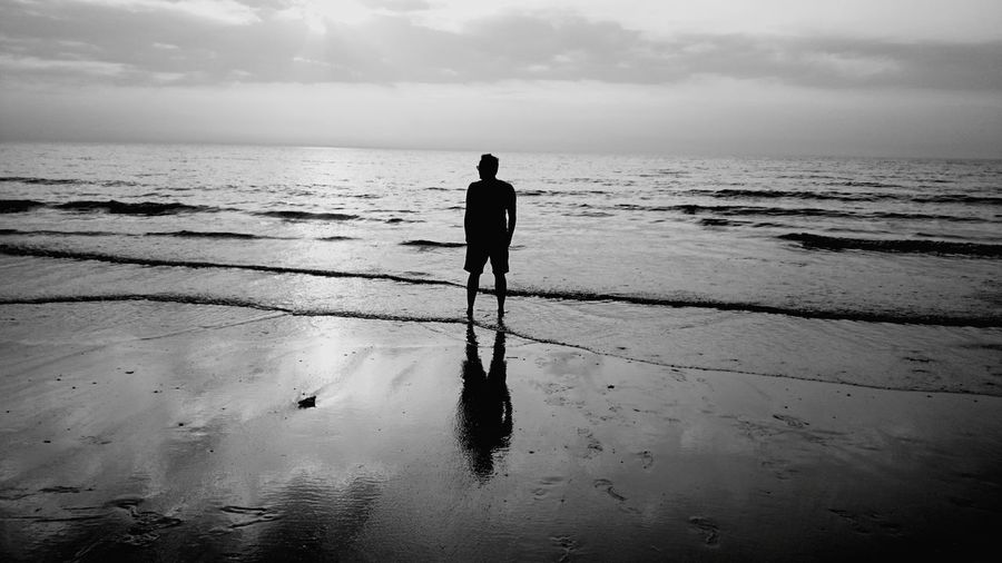 Silhouette man standing on shore at beach