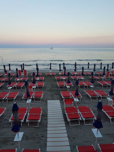 Beach Chair Sea Horizon Over Water Table Arrangement Sand Outdoors Outdoor Chair Summer Group Of Objects Red Water Large Group Of People Large Group Of Objects Relaxation People Sunset Day Vacations Sunset Sea Boat In A Row Tranquility Travel Destinations
